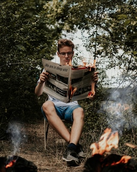 Young man sitting on a chair holding and reading a burning newspaper