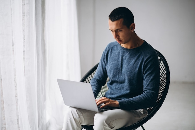 Young man sitting in chair and using laptop