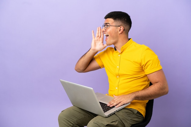 Young man sitting on a chair with laptop shouting with mouth wide open to the lateral