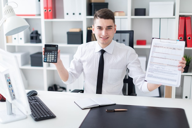A young man sitting at a computer desk in the office and holding a tablet and a calculator.