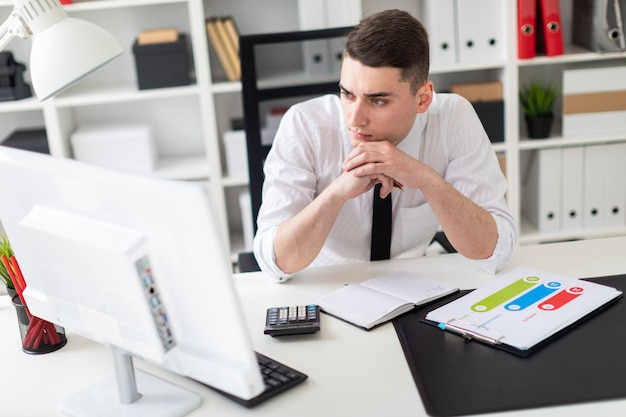 A young man sitting at a computer desk in the office and working with documents.