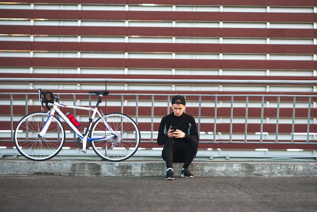 Young man sitting in a dark dress wearing a bicycle and using a smartphone on the background of a striped burgundy wall