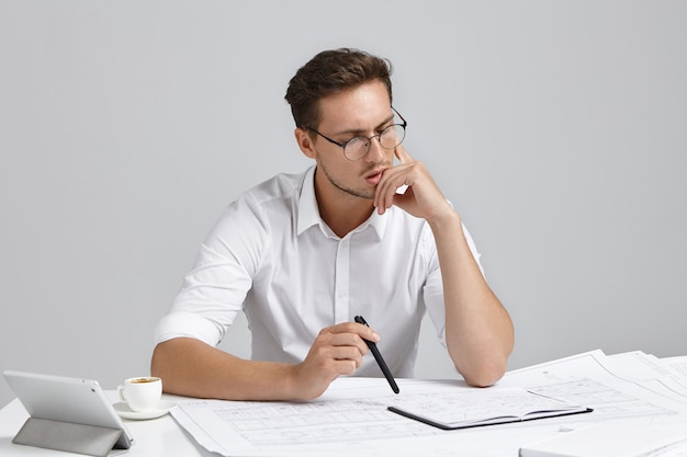 Young man sitting at desk and doing paperwork