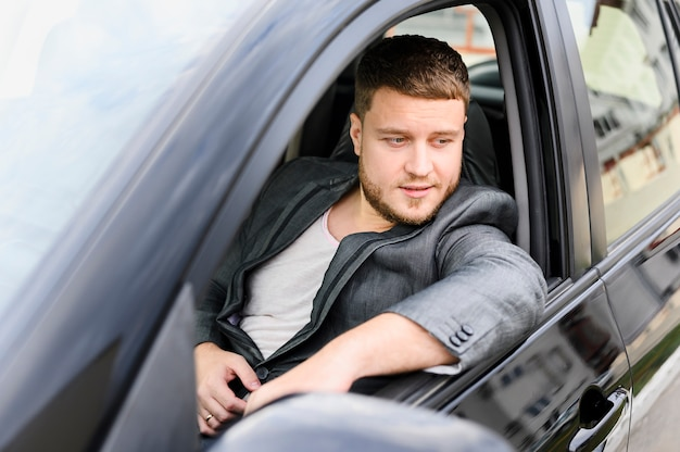 Young man sitting on the drivers seat