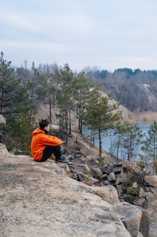 Young man sitting on the edge of a cliff