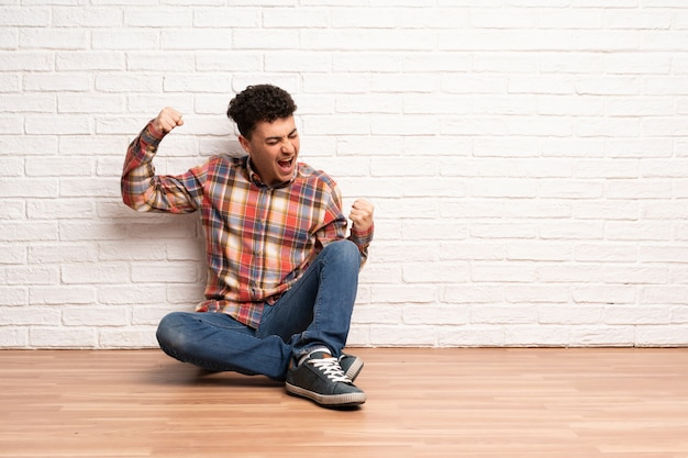 Young man sitting on the floor celebrating a victory