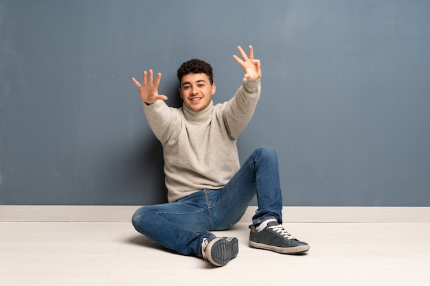 Young man sitting on the floor counting nine with fingers