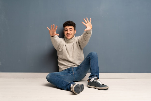 Young man sitting on the floor counting ten with fingers