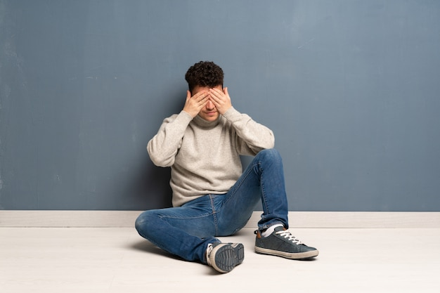 Young man sitting on the floor covering eyes by hands