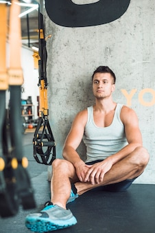Young man sitting on floor in fitness club
