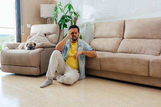 Giovane uomo seduto sul pavimento e tenendo la testa con rammarico o delusione