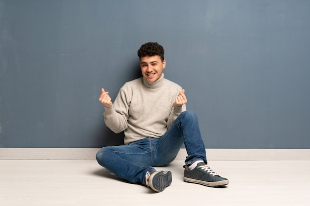 Young man sitting on the floor making money gesture