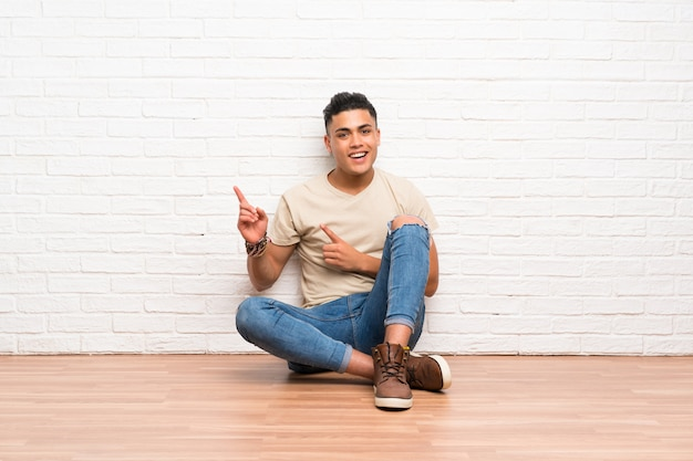 Young man sitting on the floor pointing finger to the side