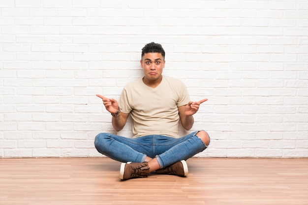 Young man sitting on the floor pointing to the laterals having doubts