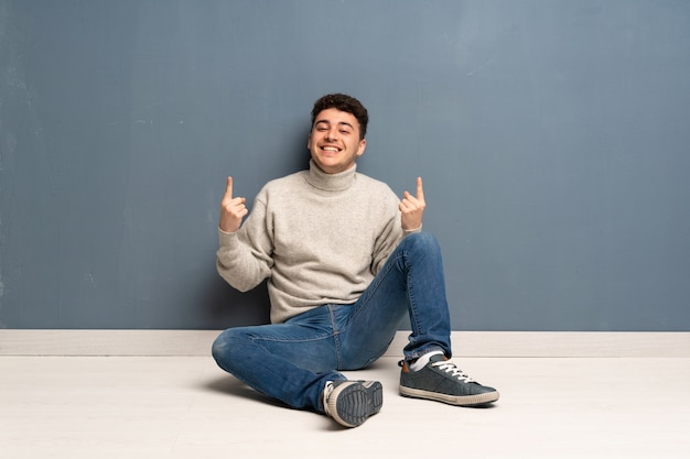 Young man sitting on the floor pointing up a great idea