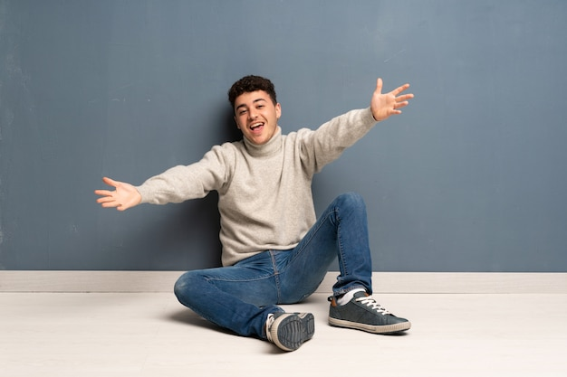 Young man sitting on the floor presenting and inviting to come with hand