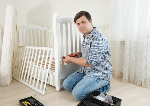 Young man sitting on floor and repairing child's bed