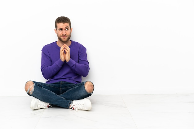 Young man sitting on the floor scheming something