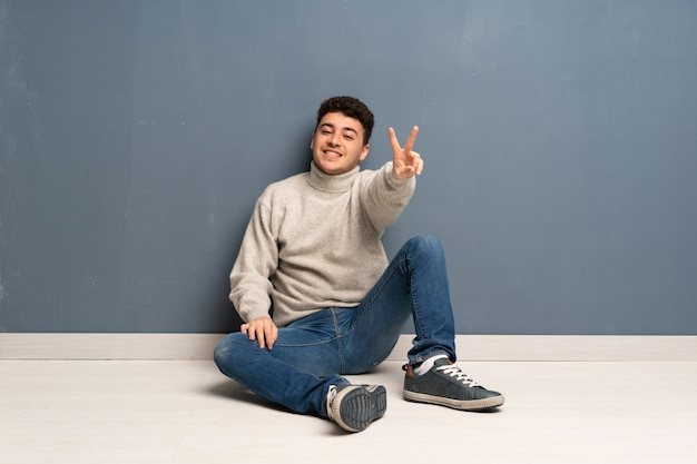 Young man sitting on the floor smiling and showing victory sign