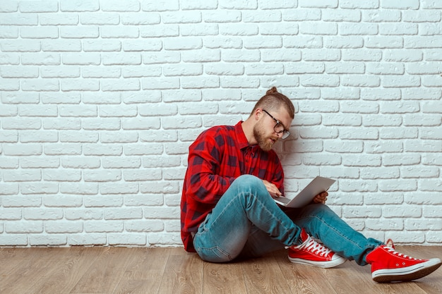 Young man sitting on floor with laptop