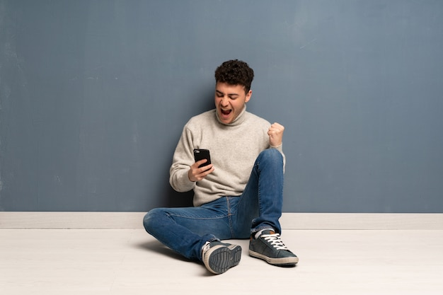 Young man sitting on the floor with phone in victory position