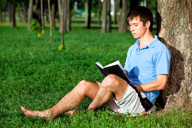 Young man sitting on green grass near tree and reading book
