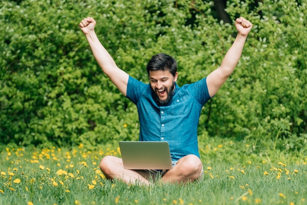 Young man sitting on green grass with raised his hands up and with laptop