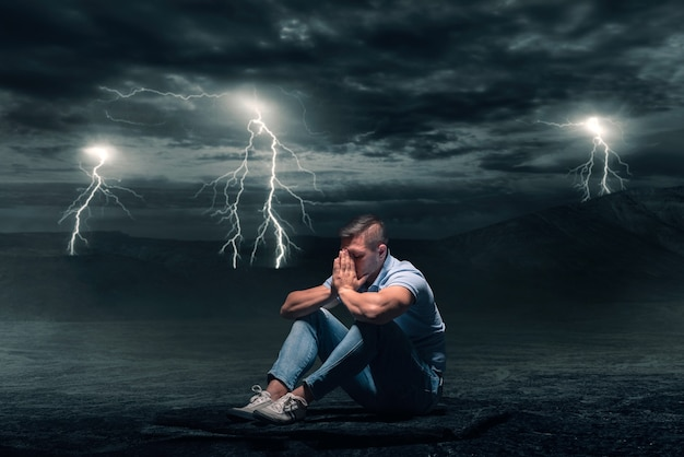 Young man sitting on the ground in desert, storm with lightning flash