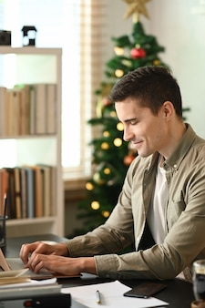 Young man sitting in home office and working online with laptop computer.