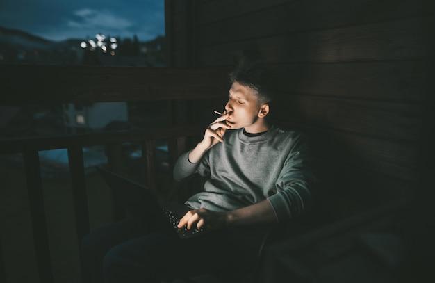 ノートパソコンを使用してバルコニーの椅子に座っている若い男
