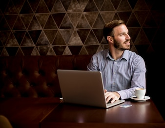 Young man sitting in cafe and using laptop