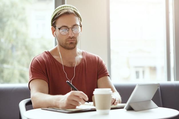 音楽を聴くカフェに座っている若い男