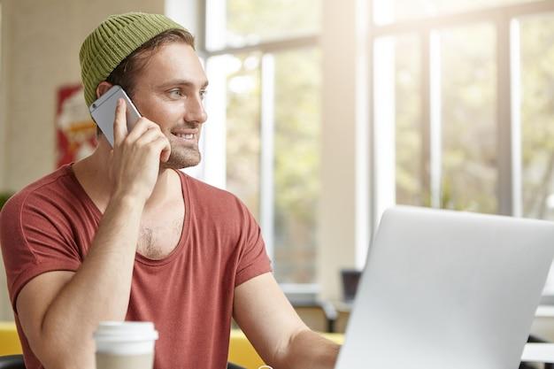 ノートパソコンと携帯電話とカフェに座っている若い男