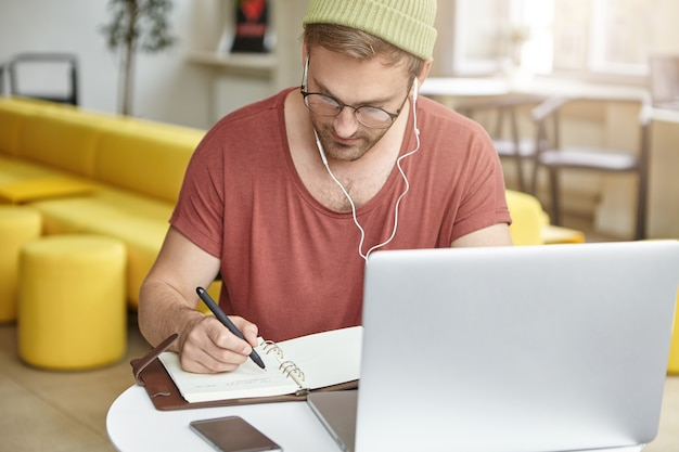 Молодой человек сидит в кафе с ноутбуком