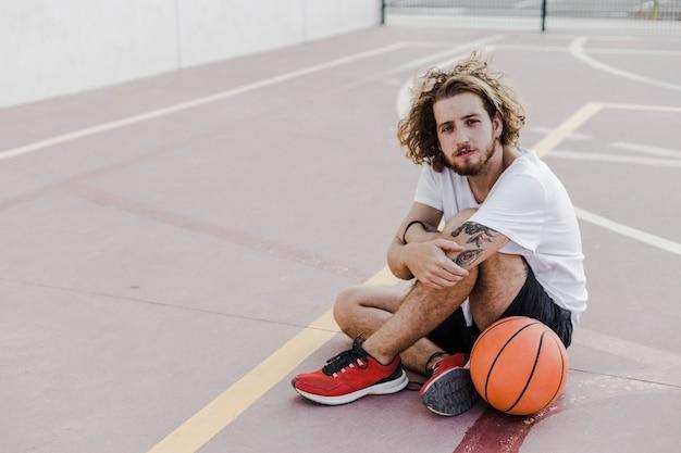 バスケットボール、コートに座っている若い男