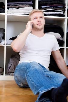 Молодой человек сидит перед своим шкафом.