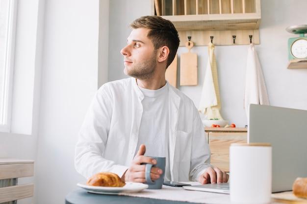 Молодой человек сидит перед столом с ноутбуком и едой, глядя через окно