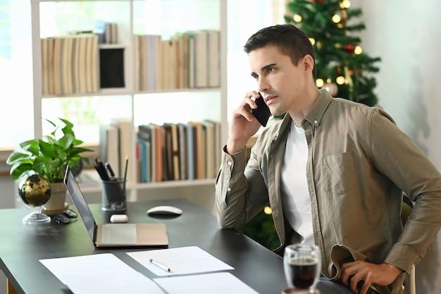 Молодой человек сидит в домашнем офисе и разговаривает по мобильному телефону.