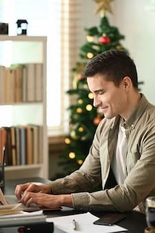 Молодой человек сидит в домашнем офисе и работает в интернете с портативным компьютером.