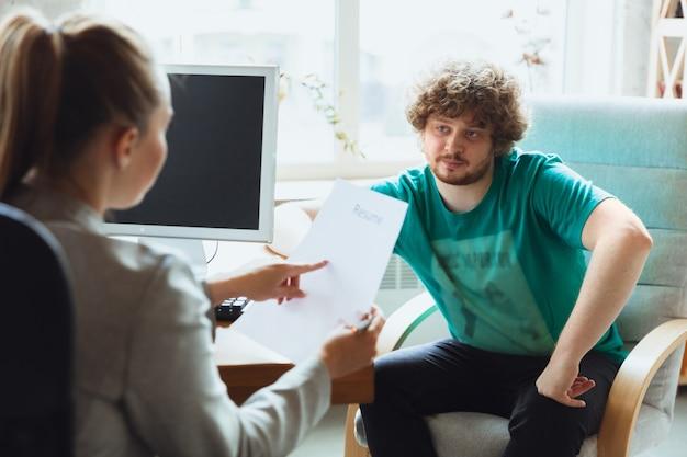 女性従業員、上司、または人事マネージャーとの就職の面接中にオフィスに座って、話し、考え、自信を持っているように見える若い男性。仕事、就職、ビジネス、金融、コミュニケーションの概念。
