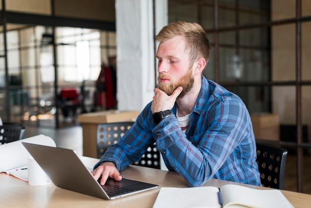 Молодой человек сидит в офисе, используя ноутбук