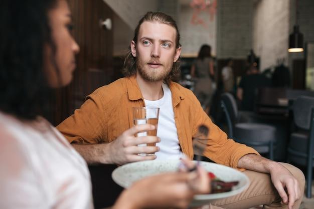 젊은 남자가 레스토랑에 앉아 여자와 이야기