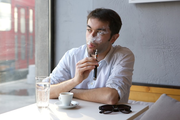 Young man sitting indoors smoking electric cigarette
