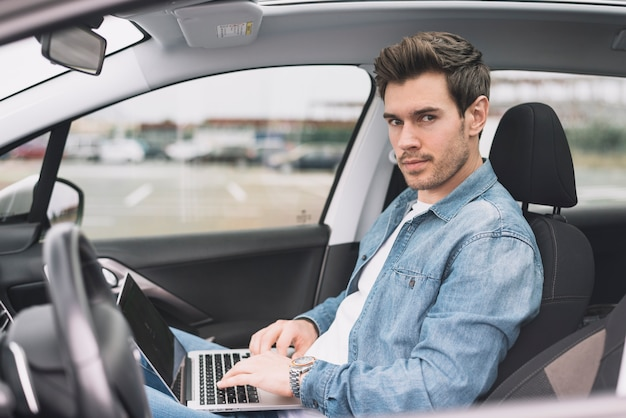 Young man sitting inside the modern car with laptop looking at camera
