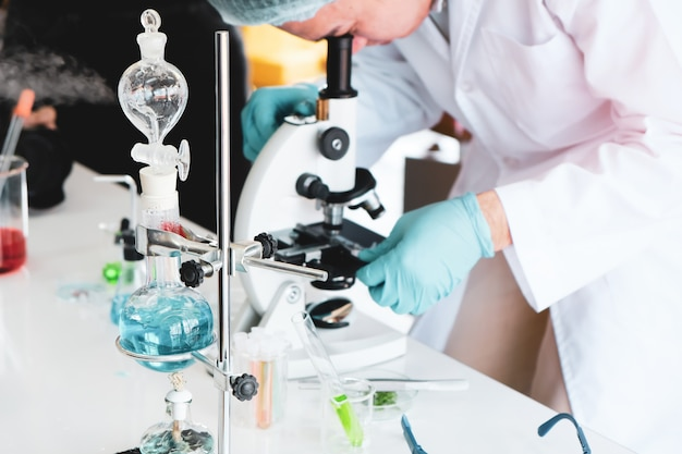Young man sitting in a lab looking through a microscope.