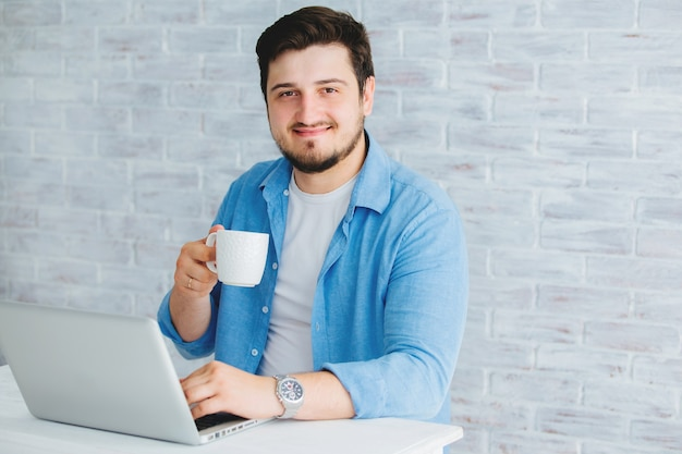 Young man sitting at a laptop in the studio with a cup of tea