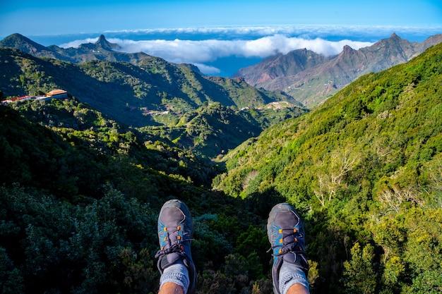 スペインのテネリフェ島の北にあるアナガ山脈を見ながら座っている若い男