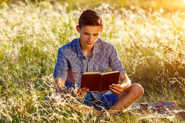 Young man sitting in nature reading a book