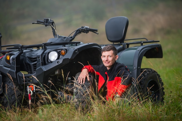 Young man sitting near four-wheeler atv
