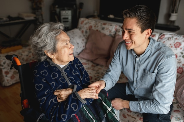 Young man sitting next to an old sick aged woman in wheelchair taking her hands while talking and smiling. family, home care concept.